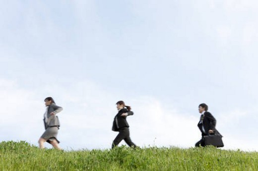 Businessman and businesswomen running on grass : Stock Photo