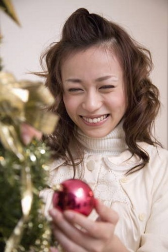 Young woman holding Christmas bauble, smiling, white background : Stock Photo