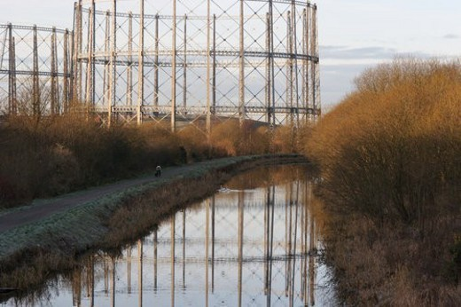 Stock Photo: 4029R-421697 Empty oil or gas  storage tanks in Glasgow Scotland, with circular girder frame reflected in river, on early frosty morning