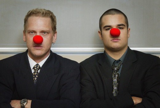 Stock Photo: 4029R-423359 Businessmen wearing as red nose looking serious
