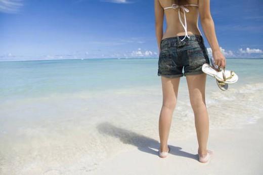 Woman standing on beach, holding sandals, Saipan, USA : Stock Photo