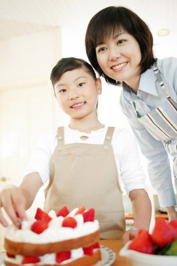 Mother and child making a cake : Stock Photo