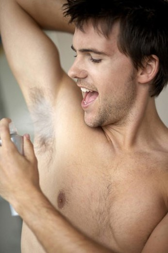 Young man applying de-odorant/anti-perspirant : Stock Photo