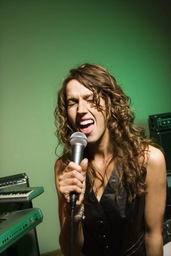 Caucasian female singning into microphone. : Stock Photo