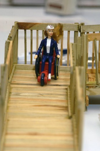Stock Photo: 4029R-427094 Barbie in a wheelchair on a doll sized wooden ramp.