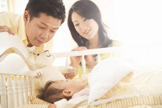 Parents gazing lovingly at their sleeping baby : Stock Photo
