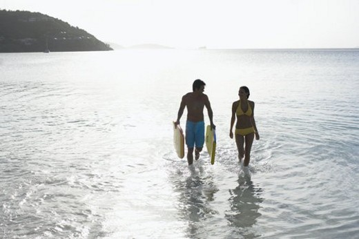 Young couple with bodyboards walking in ocean, St. John, US Virgin Islands, USA : Stock Photo