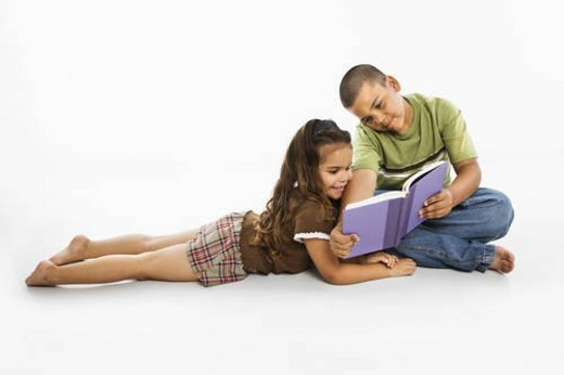 Brother and sister reading book together. : Stock Photo