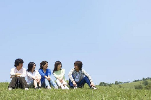 Five young people sitting on grass : Stock Photo