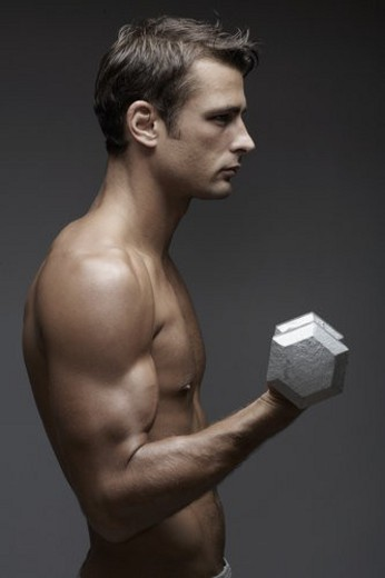 Stock Photo: 4029R-4285 Mid adult man lifting dumbbell