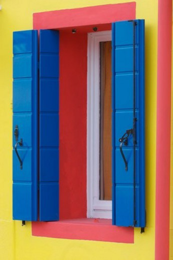 Blue shutters and red trimmed window on yellow house in Burano, Venice Lagoon Italy : Stock Photo