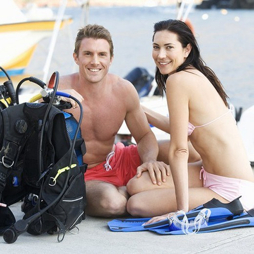 Stock Photo: 4029R-428970 A couple checking their scuba diving equipment