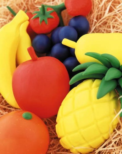 Plasticine fruit on bed of hay : Stock Photo