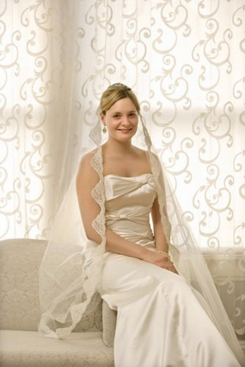 Stock Photo: 4029R-42996 Portrait of Caucasian bride sitting on love seat.