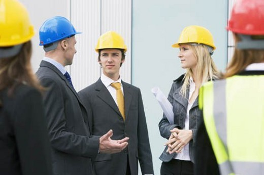 Team of construction managers visiting a property development. : Stock Photo