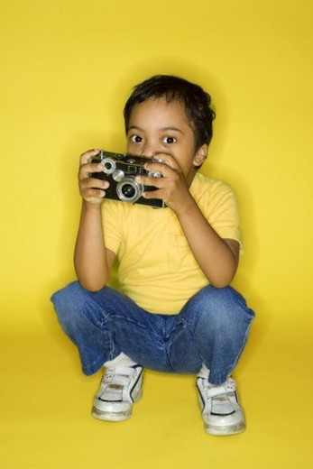 Hispanic male child kneeling with camera. : Stock Photo