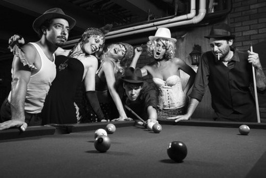 Stock Photo: 4029R-43052 Group of Caucasian prime adult retro males and females trying to distract man as he takes pool shot.
