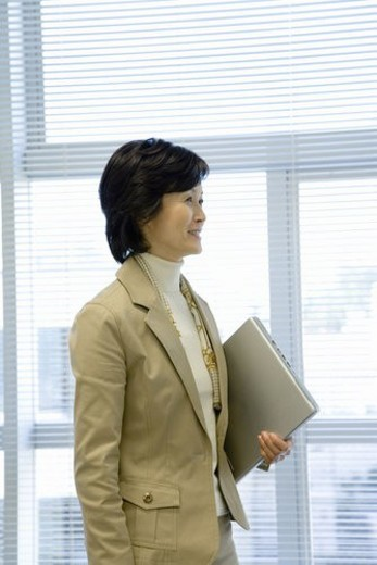 Stock Photo: 4029R-430708 A Mature Woman Holding a Laptop Computer, Side View, Waist Up