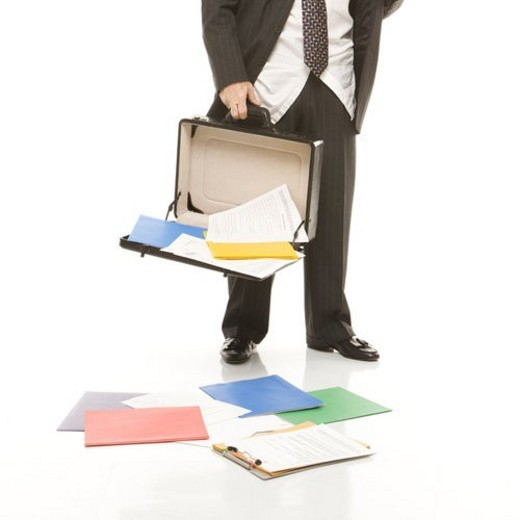 Caucasian middle-aged businessman holding open briefcase with papers falling out. : Stock Photo