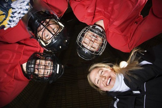 Low angle of female hockey players in huddle with coach smiling. : Stock Photo
