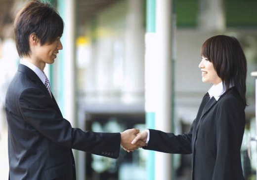 Businessman and businesswoman shaking hands in train station : Stock Photo
