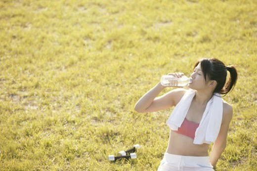 A young woman drinks water as she sits amidst grassland after her workout : Stock Photo