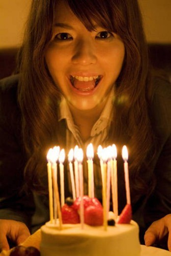 Stock Photo: 4029R-434488 Woman leaning over to blow out the candles on her birthday cake