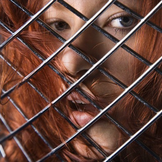 Pretty redhead young woman face behind metal pattern. : Stock Photo