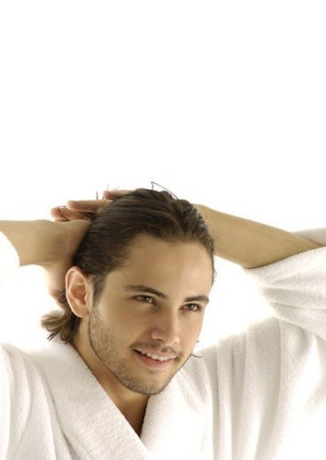 Close-up of a young man with his hands behind his head : Stock Photo
