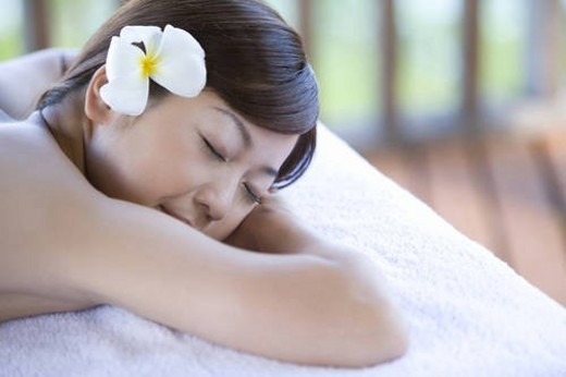 Young woman lying on massage table, Saipan : Stock Photo