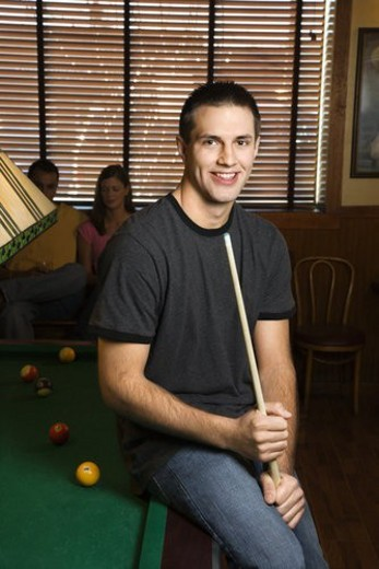 Stock Photo: 4029R-439244 Portrait of young man leaning on billiards table holding pool stick.