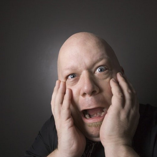 Stock Photo: 4029R-439323 Caucasian mid adult bald man with hands to face making scared facial expression.