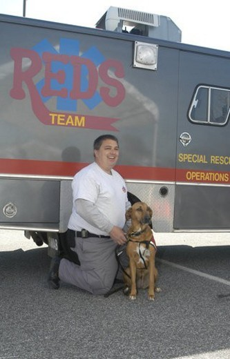 Stock Photo: 4029R-439489 Man with service dog in front of Rescue Team truck