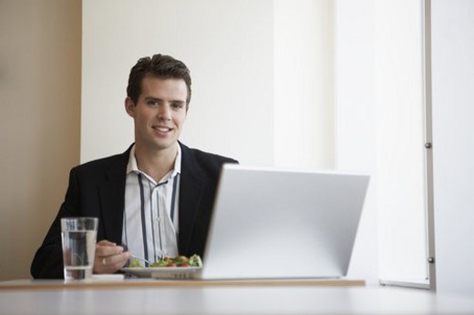 Businessman with laptop eating salad : Stock Photo