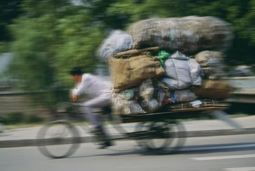 Stock Photo: 4029R-442768 Man hauling a load of bags on a cycle rickshaw in Beijing, China