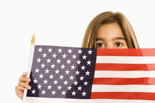 Girl peeking over American flag against white background. : Stock Photo