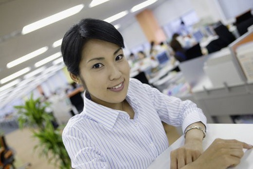 A woman sitting in her office smiles at the camera : Stock Photo