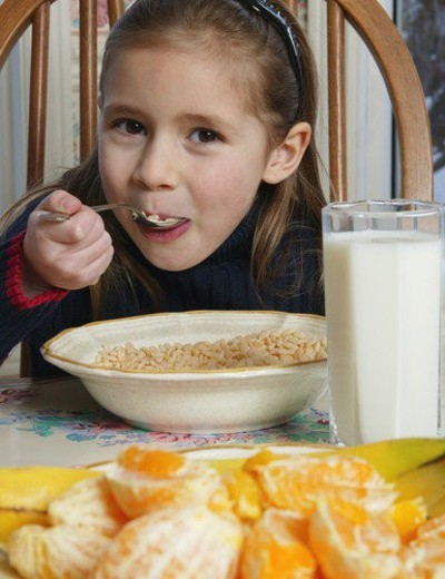 Stock Photo: 4029R-464031 Young girl eating cereal at breakfast table