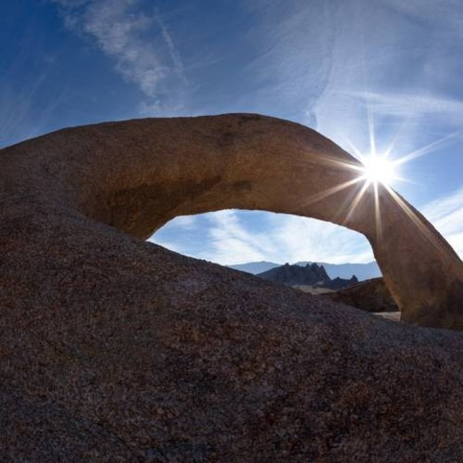 Stock Photo: 4029R-465137 Arch formation of sandstone, against blue early morning sky, with sunstar fromation, Alabama hills, with range beyond