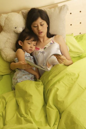 Stock Photo: 4029R-47234 Young mother and daughter reading in bed