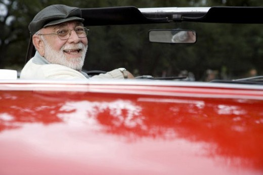 Stock Photo: 4029R-50221 A senior man driving a sports car