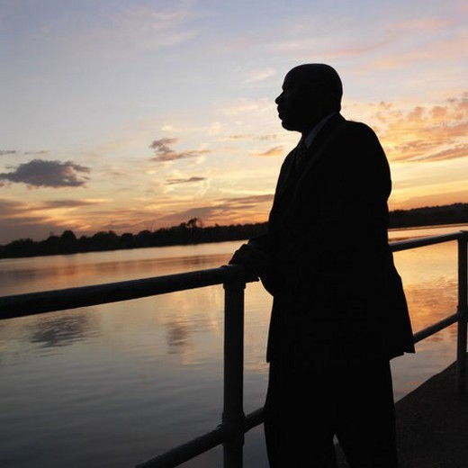 African-American man standing by water at sunset in Washington, D.C., USA. : Stock Photo