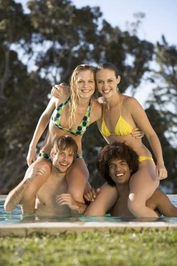 Stock Photo: 4029R-50337 Four teenage friends having fun in a swimming pool