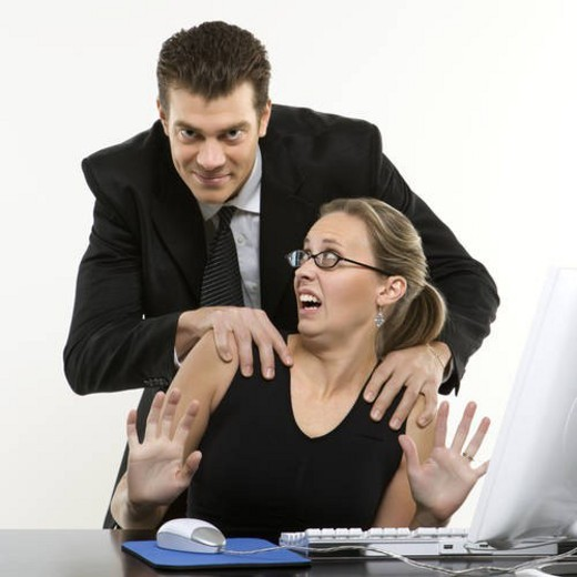 Caucasian mid-adult man sexually harassing woman sitting at computer and looking at viewer. : Stock Photo
