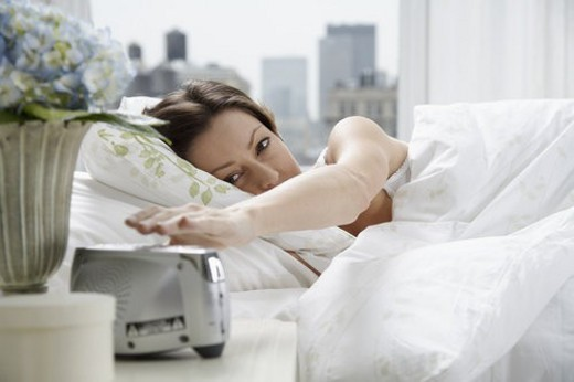 Mid adult woman reaching for alarm clock : Stock Photo