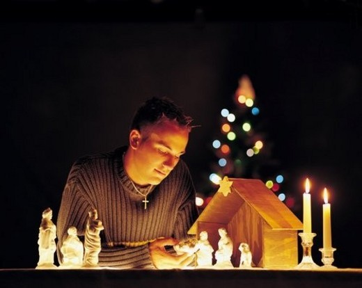 Man with nativity scene figurines and lights : Stock Photo