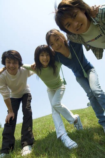 Four young people with arms around each other : Stock Photo