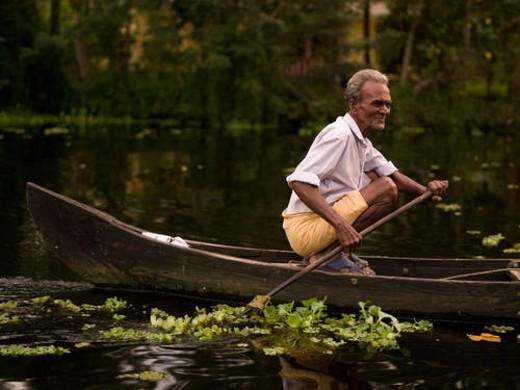 Man crouching in boat holding oar : Stock Photo