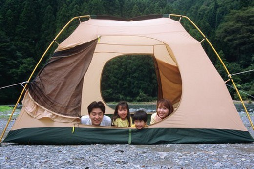 Family lying on front in a tent : Stock Photo