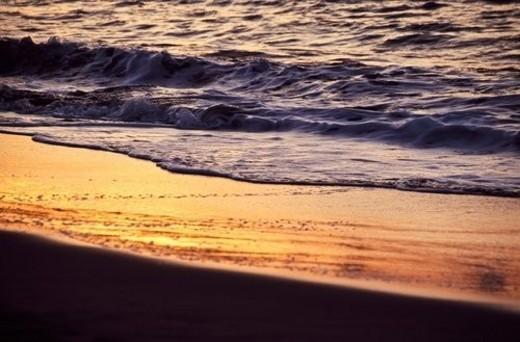 Sunset reflected on wet sand : Stock Photo